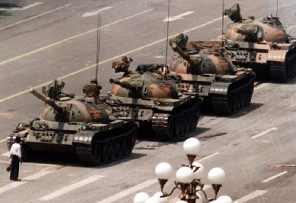 A man stands in front of a column of tanks on the the Avenue of Eternal Peace in Beijing, China, June 1989.	(Stringer/Reuters)
