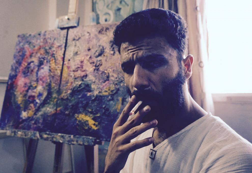 Emsallam Hdaib smokes a cigarette in his studio. Photo taken by the author.